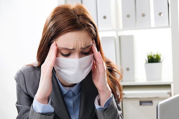 Больная коммерсантка в защитной медицинской маске на офисе Premium Фотографии