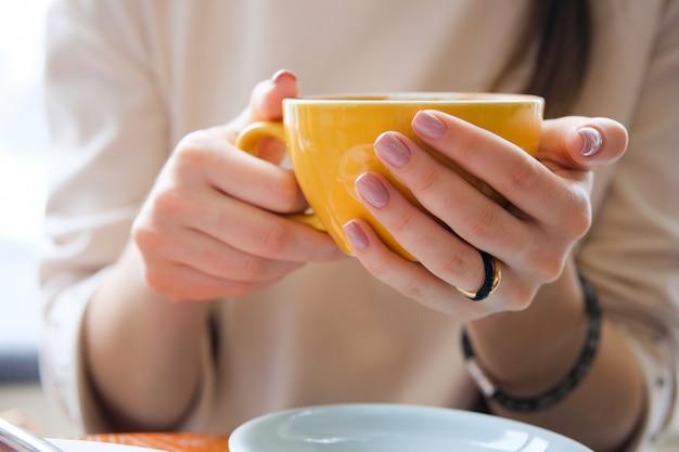 若い女性の手の中に黄色のマグカップ。カフェで一杯のコーヒーを保持している女の子。コーヒーブレイク、朝食。 Premium写真