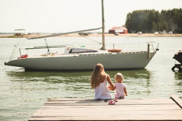 小さな女の子と彼女の母親は、晴れた夏の日に桟橋に座っています。彼らは金髪で、白い服を着て、白いヨットを見ています Premium写真