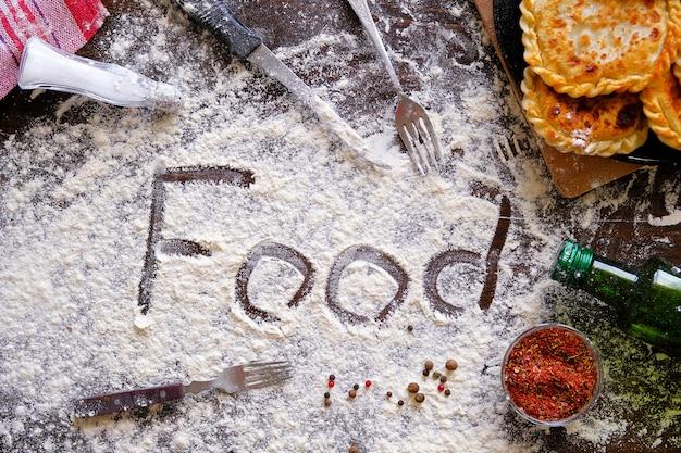 英語の碑文や単語の食べ物は、小麦粉を振りかけた。次に揚げたパイ、ナイフ、フォーク、スパイス、台所用品。料理、ベーキング、ホームベーカリーの概念。 Premium写真