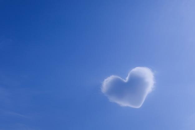 美しいのどかな青い空、愛のシンボルに対するハートの形をした白い雲。想像力、バレンタインデーの背景の概念 Premium写真