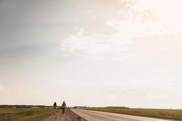 愛のカップルは田舎道です。ヒッチハイクの概念背面図テキスト用のスペースをコピーします。 Premium写真
