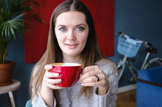 カフェに座って、カプチーノのカップを持って、カメラを見て、楽しんで、街の通り、ロマンチックな夕食、日当たりの良い若い美しいスタイリッシュな女性。コーヒーを飲む女の子。朝ごはん。コーヒーブレイクあたたかい Premium写真