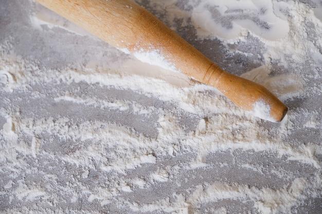 散在小麦粉と軽い木製のテーブルの上の麺棒。ホームキッチンで焼く、調理するプロセス。料理中毒の概念、料理。 Premium写真