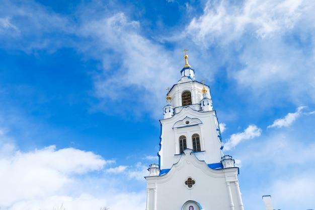 雲と青い空を背景に教会の塔。ロシア、チュメニ。 Premium写真
