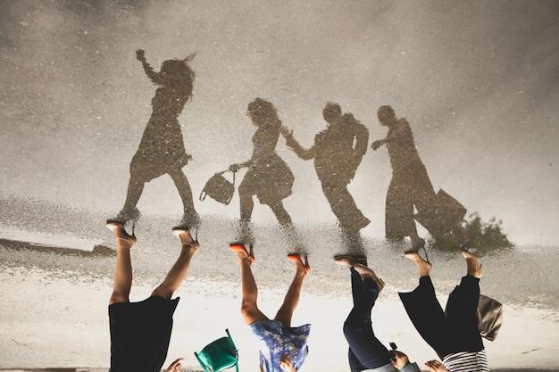 道路上の水たまりに人々のグループの反射。 Premium写真