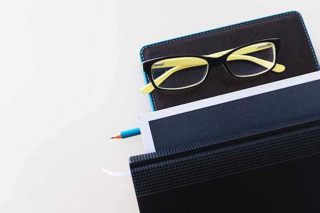 ノート、鉛筆、めがね、書籍の山。 Premium写真