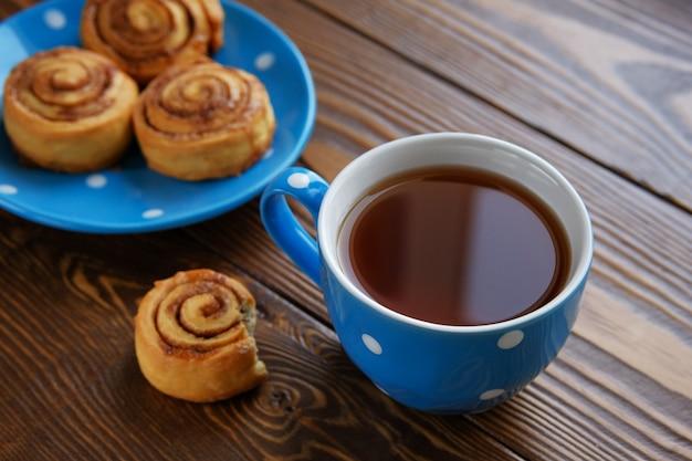 自家製シナモンロールは木製のテーブルの上の青い皿の上にあります。 Premium写真