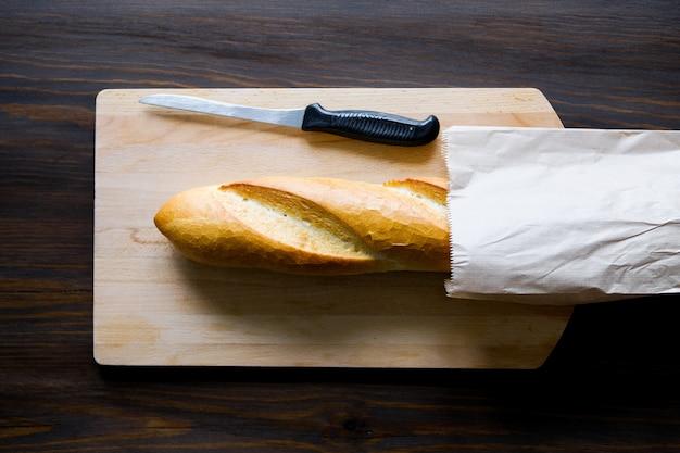 Свежеиспеченный хлеб в бумажном пакете на деревянном столе Premium Фотографии