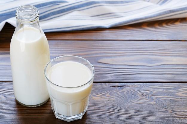 ガラス瓶と木製のテーブルの上のガラスのミルク。 Premium写真