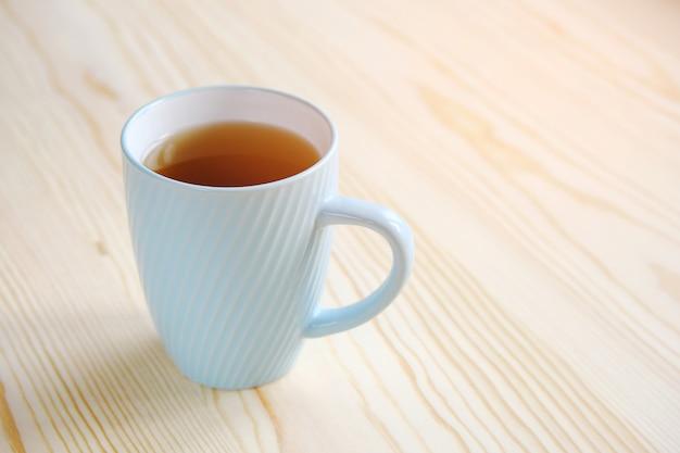 木製のテーブルのクローズアップに紅茶のマグカップ。 Premium写真