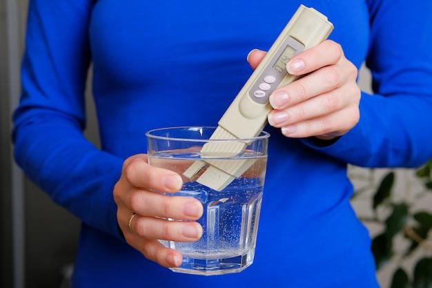 女子ラボが水質管理を決定するデジタルテスターの手の中に。 Premium写真