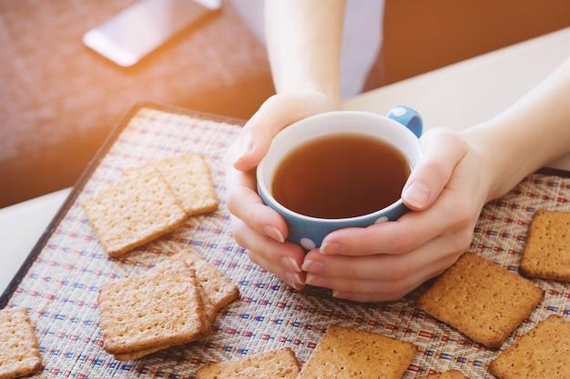 熱いお茶やコーヒーのカップを保持している女性、クッキーの横にあるクローズアップ Premium写真