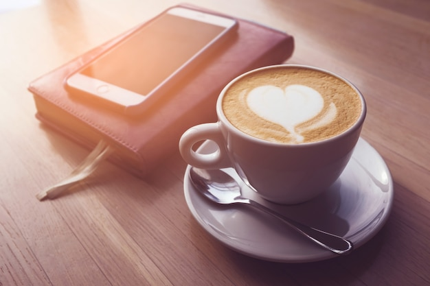 木製のテーブルの上のカフェには、カプチーノ、ラップトップ、携帯電話、ノート、日記のカップがあります。 Premium写真