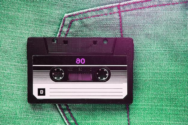 Винтажная ретро аудиокассета на фоне зеленых джинсов Premium Фотографии