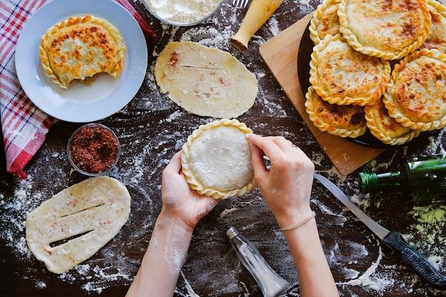 生の生地からグルジアのパンを料理人の手で。女性はケーキやカチャプリを作ります。 Premium写真