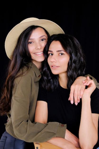 モデル、女の子の姉妹、ブルネットの友人、カメラ目線、笑顔、楽しんで、ハグ。 Premium写真