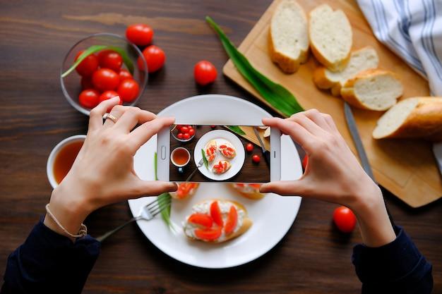 スマートフォンで朝食の写真を撮るブロガー Premium写真