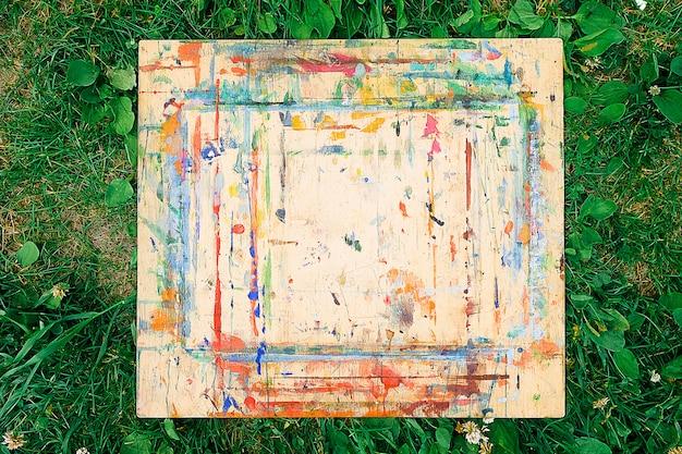 木の板は、緑の草の上に横たわって、明るいペンキで汚されて飛び散っています。上からの眺め。織り目加工の背景。 Premium写真