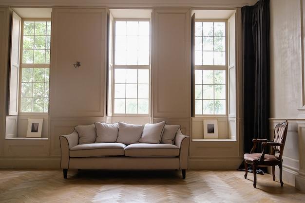 ソファ、アンティークの椅子、大きな窓があるクラシックなインテリア。 Premium写真