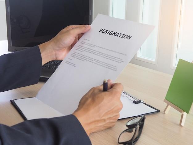机の上に座っているエグゼクティブ。従業員辞任書を読む。 Premium写真