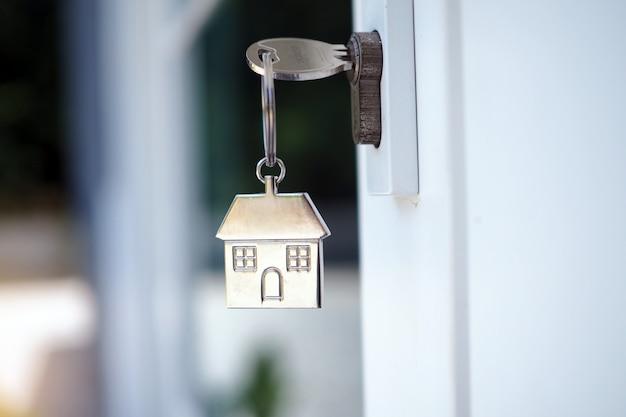 新しい家のドアの鍵を開けるための家の鍵。家を借りる、買う、売る Premium写真