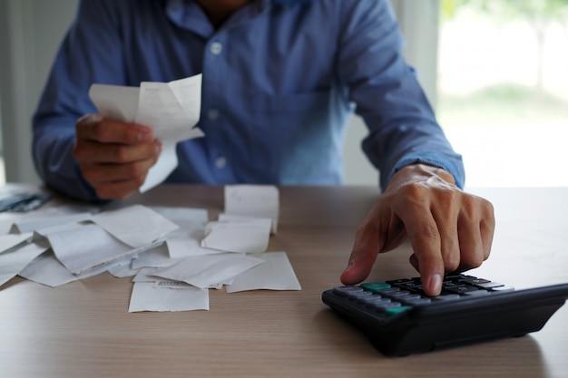 ビジネスマンは電卓を使用してテーブルに置かれた請求書を計算します。借金の概念 Premium写真