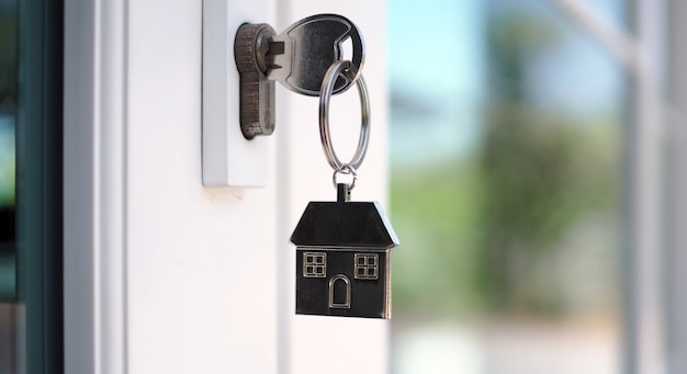 Ключ от дома для разблокировки нового дома вставлен в дверь. Premium Фотографии
