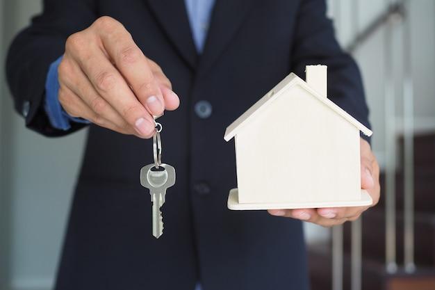 Страховые продавцы держат модели домов и ключи Premium Фотографии