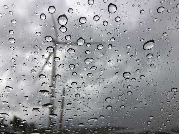 車のガラスに雨が降る外は風車の景色です。悲しい、孤独な背景 Premium写真
