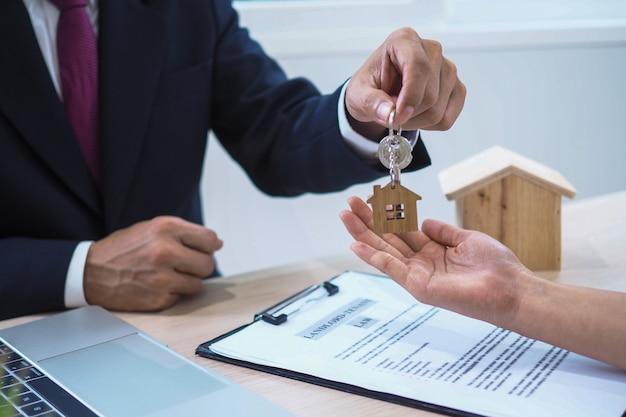 住宅購入者は販売者から家の鍵を受け取っています。家を売り、家を借りて、アイデアを買いましょう。 Premium写真