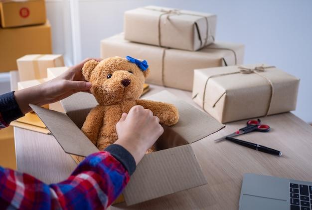 若いビジネス女性は、オンラインショッパーに商品を届けるための箱を準備しています。 Premium写真