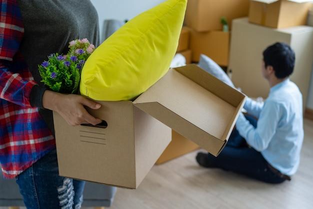 Жена несет коробку для личных вещей, а муж упаковывает коробку. Premium Фотографии