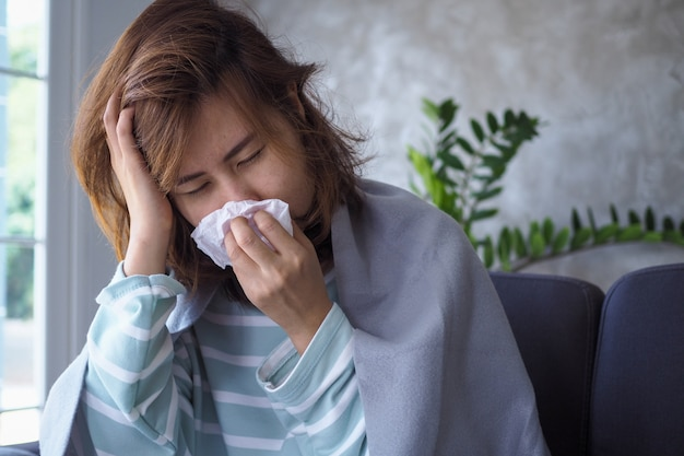 アジアの女性は、高熱と鼻水があります。病気の人の概念 Premium写真