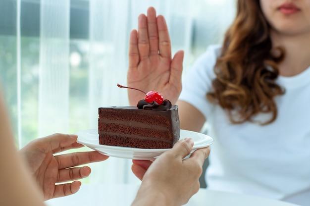 女性はチョコレートケーキでプレートを押す Premium写真