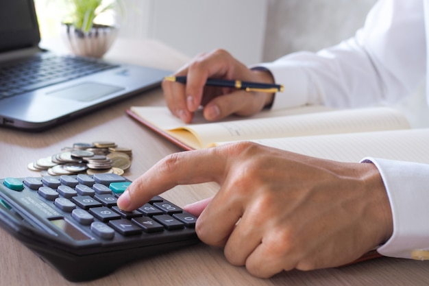 Азиатская работа бизнесмена с калькуляторами для вычисления информации о счете Premium Фотографии
