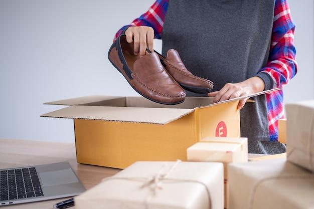 Интернет-продавцы упаковывают обувь в коробку, чтобы доставить товар покупателям, заказанным на сайте Premium Фотографии
