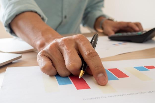 Бухгалтер проверяет отчеты о расходах и инвестициях компании по представленным документам. Premium Фотографии