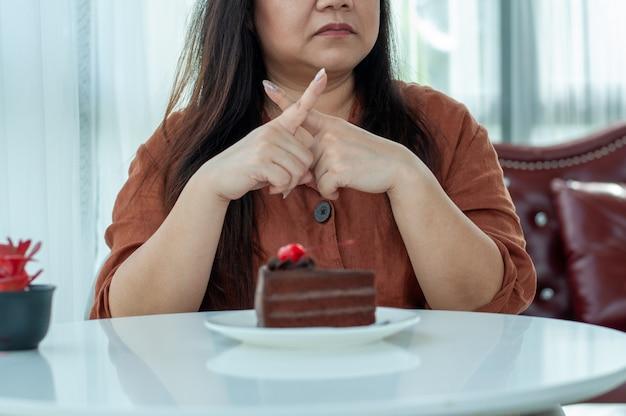 女性はチョコレートケーキを食べることを拒否しました Premium写真