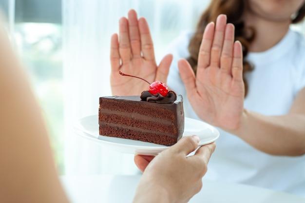 女性はケーキプレートを押しのけます Premium写真