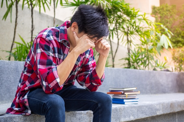 試験結果の不合格について心配して座っているアジアの男子生徒が強調しました。 Premium写真