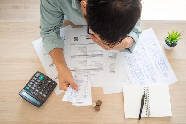 執事の心配する手が額に触れ、電気代、インターネット代、携帯電話代、クレジットカード代など手元に多くの費用がかかります。借金の概念 Premium写真