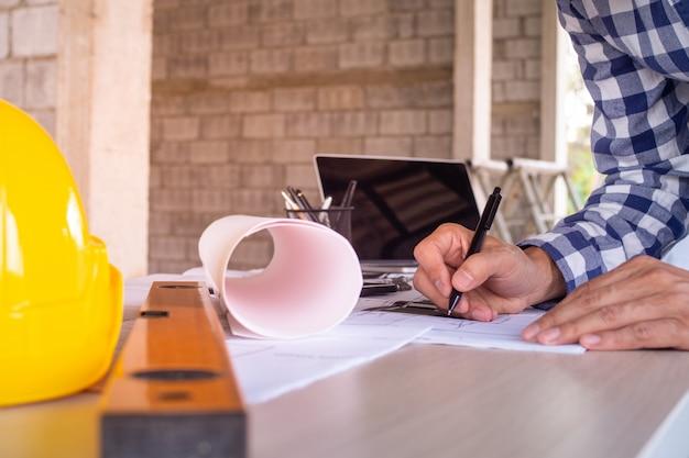 Инженер готовит проект, пишет проект, записывает его на бумаге, чтобы проверить и отремонтировать дом перед продажей заказчику. Premium Фотографии