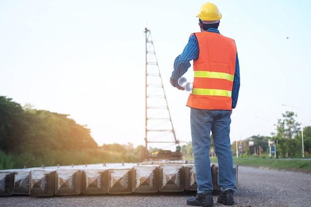 エンジニアは彼の手に青写真を握り、建築区域のクレーンを見て Premium写真