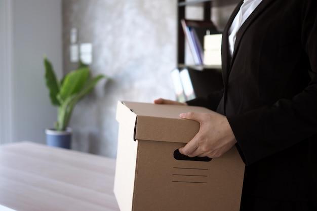 実業家は、私物と辞任の手紙のためのボックスを保持します。 Premium写真