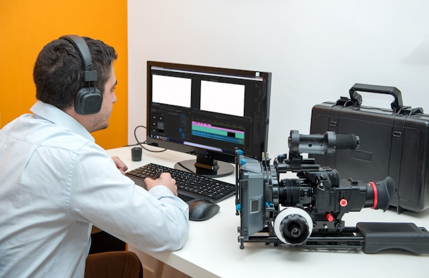 Молодой человек дизайнер с помощью графического планшета для редактирования видео Premium Фотографии