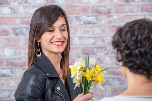 若いブルネットの女性は水仙の花束を提供しています Premium写真