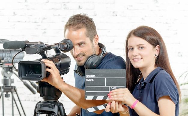 Оператор и молодая женщина с кинокамерой и колотушкой Premium Фотографии