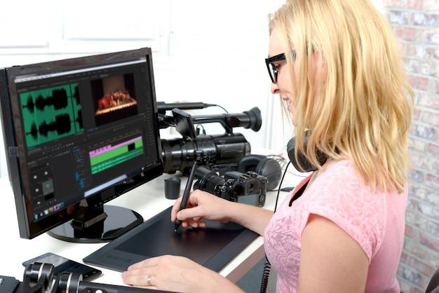Молодая женщина дизайнер, используя компьютер для редактирования видео Premium Фотографии