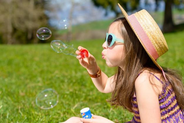 シャボン玉を作る少女 Premium写真